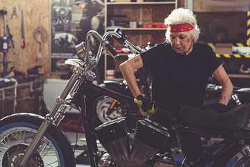 Calm female pensioner polishing bike in mechanic shop