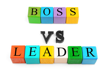Lines of colorful wooden cubes and black letters forming text BOSS VS LEADER isolated on white