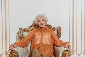 Happy old woman sitting on armchair