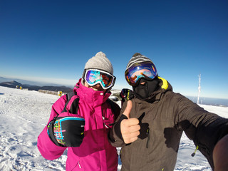 Female and male show's thumb up on skiing