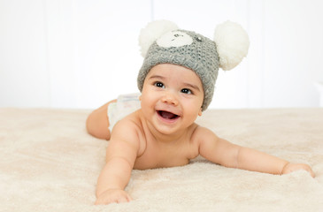 Beautiful baby boy in bed with a funny hat