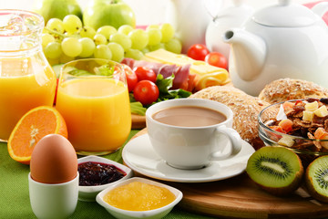 Breakfast served with coffee, orange juice, egg and fruits