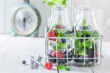 Fresh water in bottle with berries and mint leaves