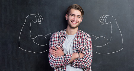 Young man against the background of depicted muscles on chalkboard