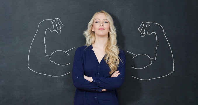 Young woman against the background of depicted muscles on chalkboard
