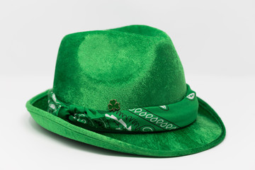 A green suede fedora hat with bandana and clover pin isolated on white background.