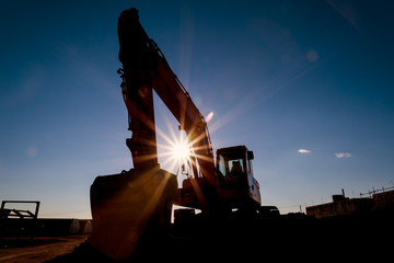Silhouette of the excavator on the construction site