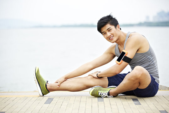 young asian man exercising outdoors sitting on ground stretching legs