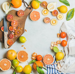 Natural fresh citrus fruits slices on wooden rustic cutting board over grey marble table background, top view, copy space