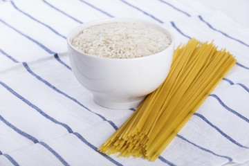 Bowl of white raw rice and handful of spaghetti pasta