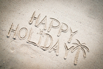 Happy Holiday written in the sand on the beach