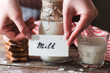 Naming bottle of milk with cookies closeup. Female hands put card with word milk near it. Tasty snack, healthy lifestyle, calcium, natural organic drink concept