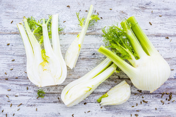 Fresh and raw fennel bulbs on wooden background.