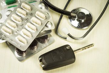 Car keys on the background of pills and a stethoscope