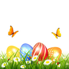 Butterflies flying over Easter eggs on grass