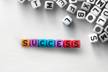colorful SUCCESS english alphabet cube on white paper background