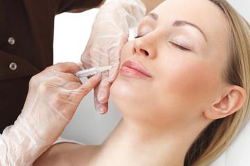 Powiększanie ust.  Kosmetyczka wstrzykuje wypełniacz w usta