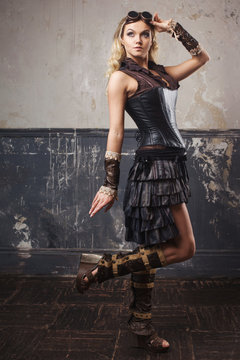 Portrait of pretty beautiful steampunk woman in Aviator glasses over grunge background.