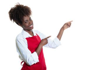 Afrikanische Kellnerin mit roter Schürze zeigt zur Seite