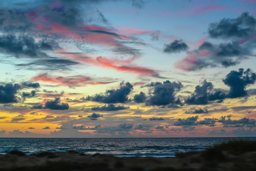 Pink clouds over the Sea in Israel. Dramatic sky in blue, orange and purple colors over the ocean. Colorful Twilight, sunset, dawn, sunrise - stunning views of nature, landscape.