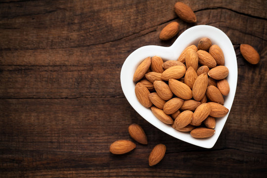 Almonds in a white heart shaped bowl against dark rustic wooden background. Overhead view