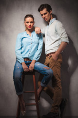 standing casual man is leaning elbow on seated girlfriend