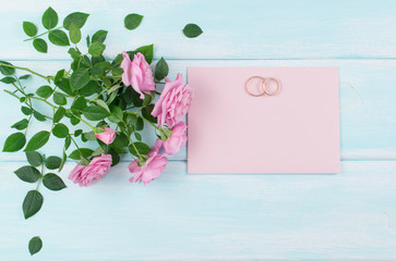 Pink roses and bridal rings with paper greeting card for wedding on background of shabby wooden planks.