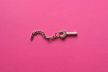 Golden key on a pink background.