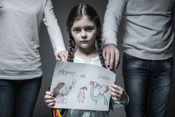 Little sad girl standing between her parents