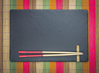 Chopsticks on black slate coaster on multicolored bamboo scroll mat. Japanese style food background.  Top view with copy space