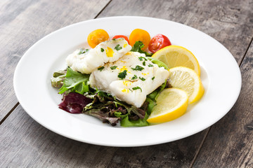 Fried cod fillet and salad in plate on wooden background