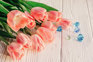 beautiful pink tulips with blue gemstones on white rustic wooden background. tender view of spring flowers in soft morning sunny light with space for text. blogging advertising concept
