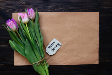 Bouquet of beautiful fresh tulips with paper on the wooden background.