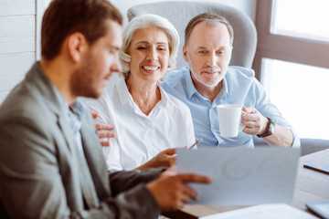 Positive aged couple meeting with insurance agent