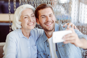 Cheerful aged woman and her grandson making selfies