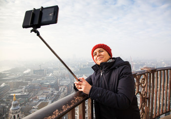 woman taking a selfie from the rooftop of St Paul's Cathedral on a foggy day in London - city break - tourism concept