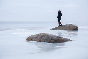 Young woman on the ice at the seashore feels the freedom in winter afternoon.