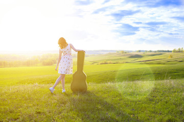 Woman walking in green field with acoustic Guitar