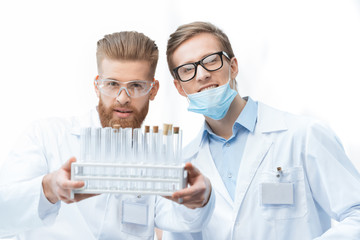 Young men chemists in lab coats holding test tubes and smiling at camera