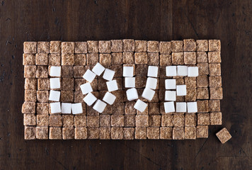 word love made of brown and white sugars , top view