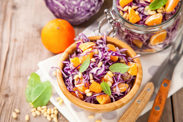 Red cabbage tangerines and pine nuts salad. Selective focus. Copy space.
