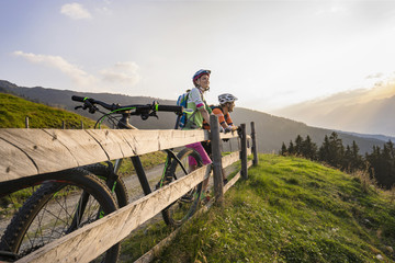 Young couple of mountain bikers standing by wooden fence looking at view during sunset, Zillertal, Tyrol, Austria