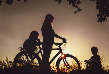 mother with son and daughter riding bike at sunset