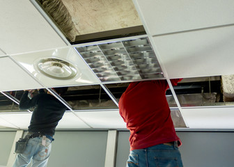 Builders putting or repairing up a suspended ceiling