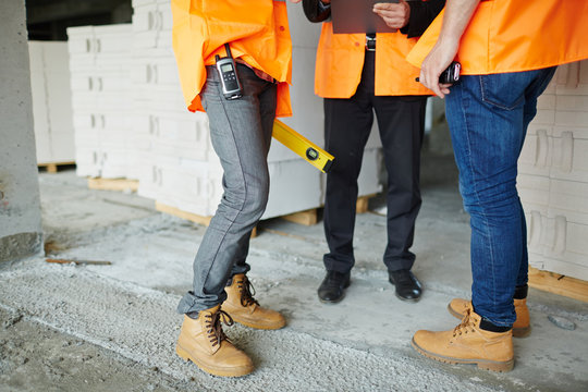 Low section shot of legs of two construction workers wearing jeans and brown leather work boots standing with man in suit on concrete floor