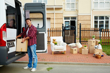 Portrait of smiling man unloading cardboard boxes from transportation van in driveway of his new big house