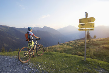 Rear view of mountain biker standing in the alpine landscape and looking at view during sunset, Zillertal, Tyrol, Austria