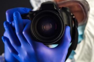Crime scene forensics investigator with digital camera
