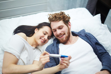 Obraz Married couple looking at positive pregnancy-test - fototapety do salonu