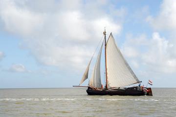 een houten zeilboot vaart op zee
